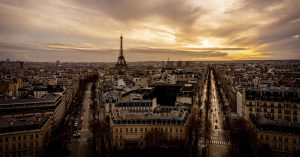 Picture of the city of Paris from the Arc de Triomphe showing the Eiffel Tower and two main streets with the sunset in the background.
