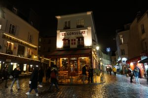 Picture of Le Consulat restaurant and two side streets with Christmas lights at night in the Montmarte neighborhood of Paris, France.