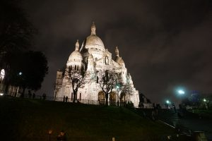 Picture of a lit-up Sacre Coeur Basilica and steps on a cloudy evening in Paris France.