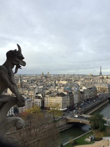 Picture of a gargoyle, the rooftops of Paris and the Eiffel Tower from the towers of Notre Dame Cathedral.