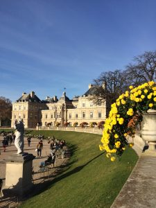 Picture of yellow flowers, a statue, and the Luxembourg Palace in the Luxembourg Gardens in Paris, France.