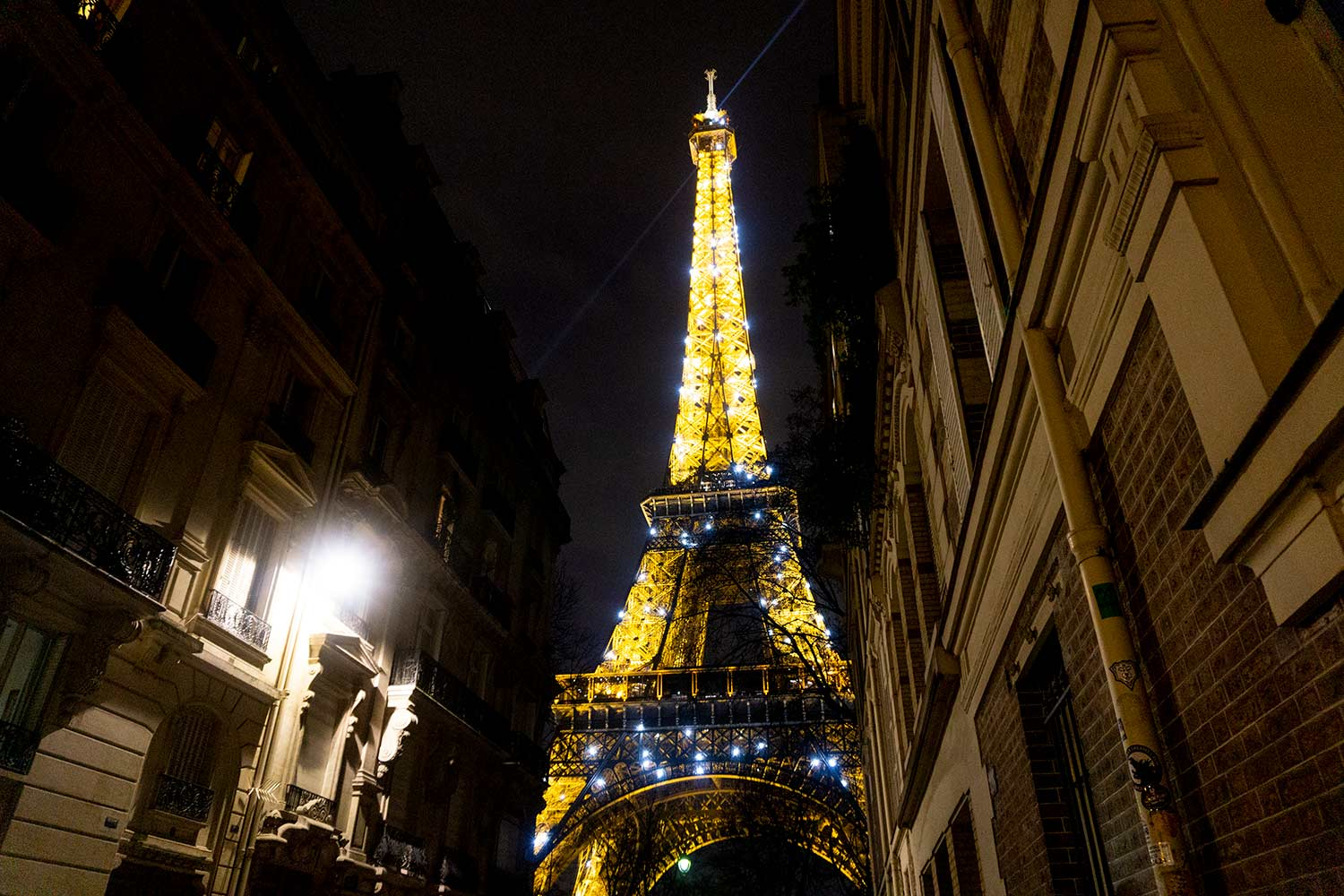 Night picture of the twinkling Eiffel Tower from a side street in Paris, France.