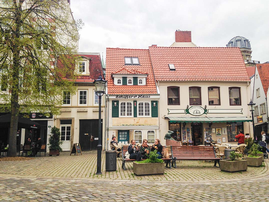 A plaza in Bremen, Germany with red roofed, colorful houses.