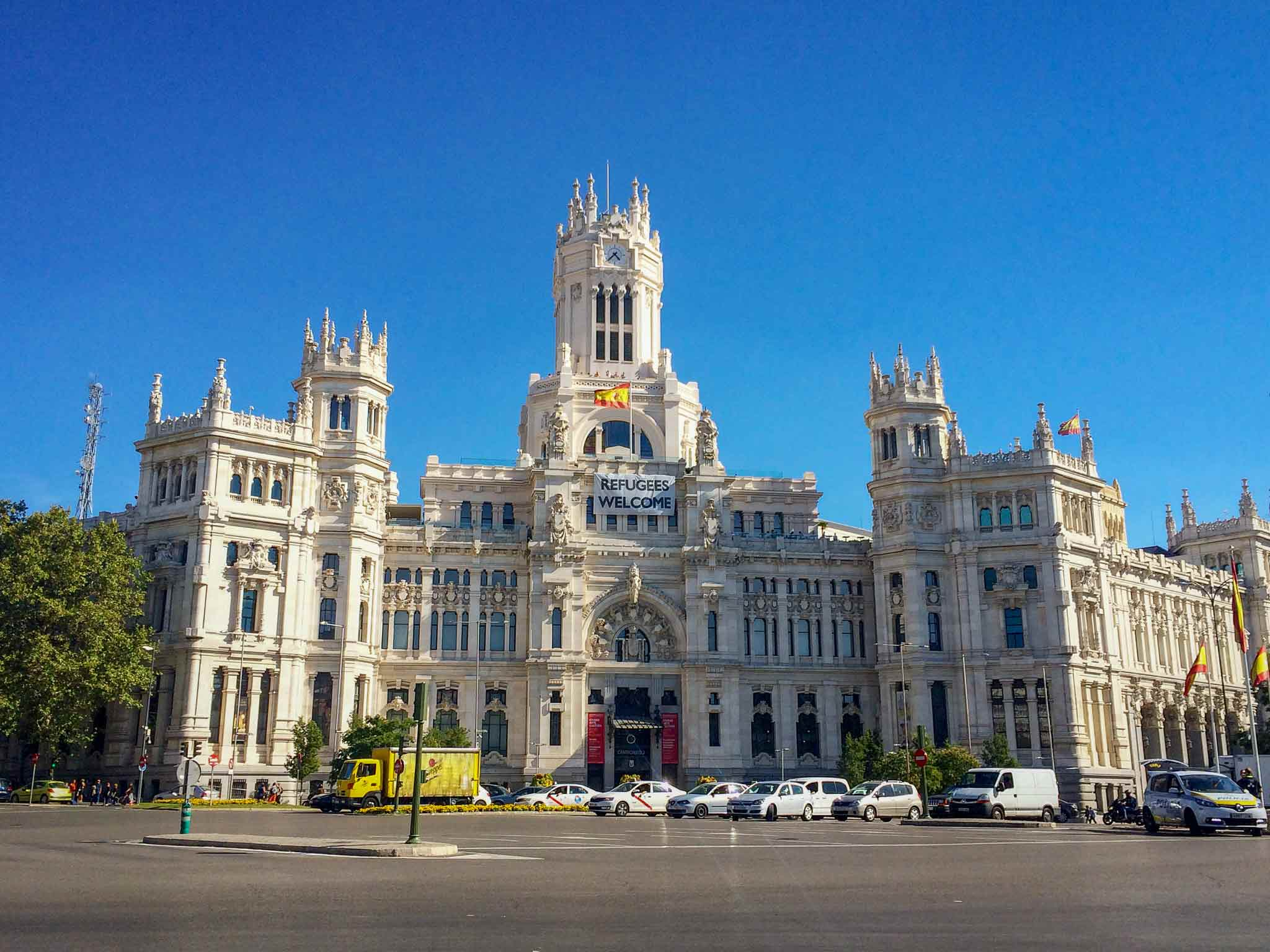 Picture of Cibeles Palace with a Spanish flag blowing in the wind and a refugees welcome sign in Madrid, Spain.