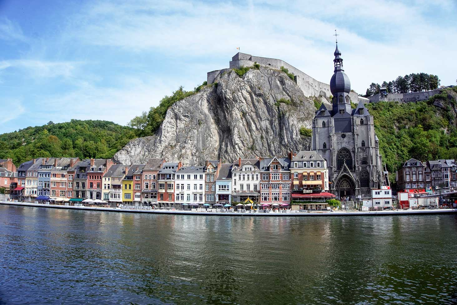 The village of Dinant, Belguim located on a river with a rock behind it.