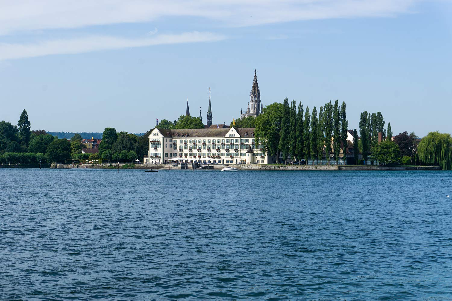 Lake Konstanz with a view of a medieval building and trees in the distance.
