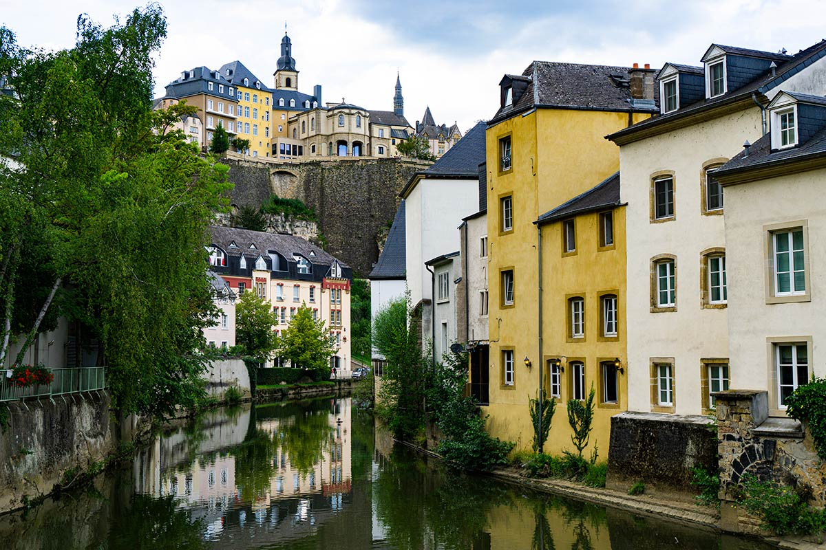 Colorful old houses lining a river in Luxembourg City. There are also houses and a church on the ramparts.