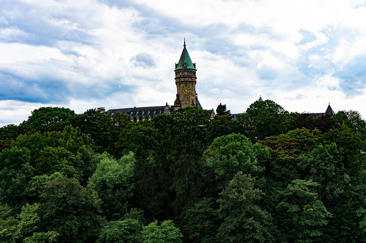 A tower poking out from the trees in the valley of Luxembourg.