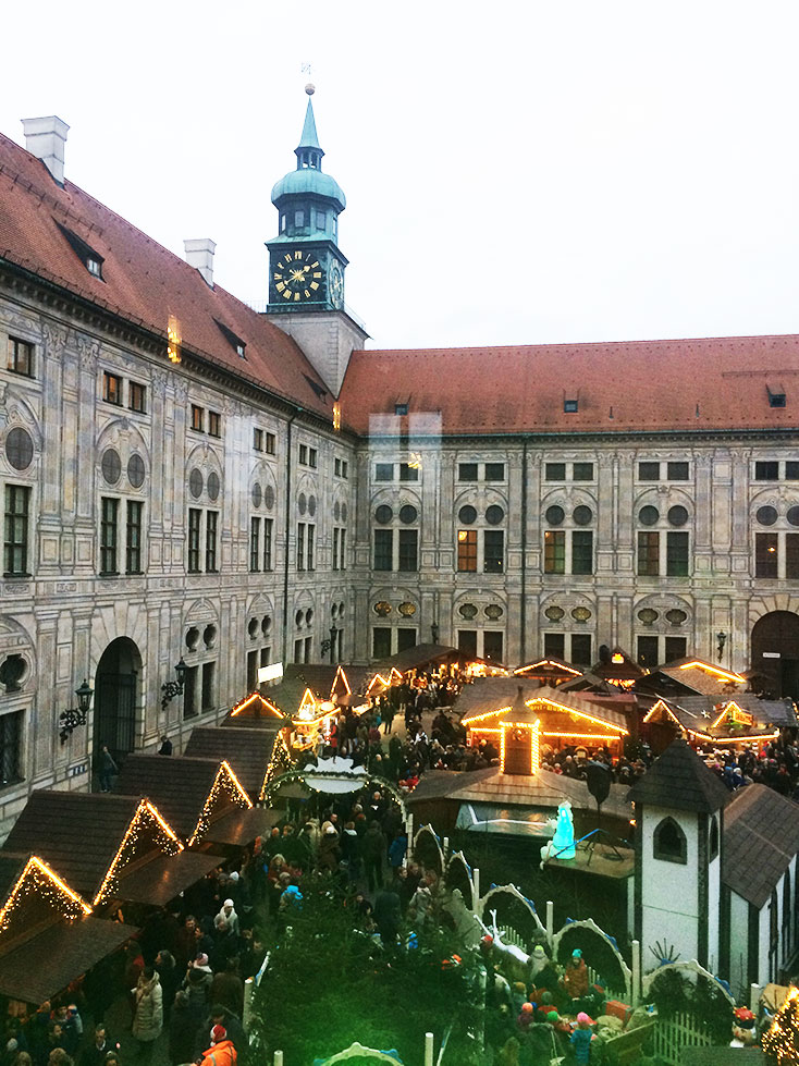 The Residenz Christmas Market in Munich, Germany with vendors and lights.