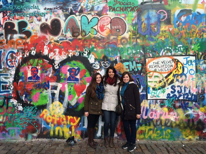 Three friends in winter clothes stand in front of the Lennon Wall in Prague, Czech Republic. The wall is full of colorful street art.
