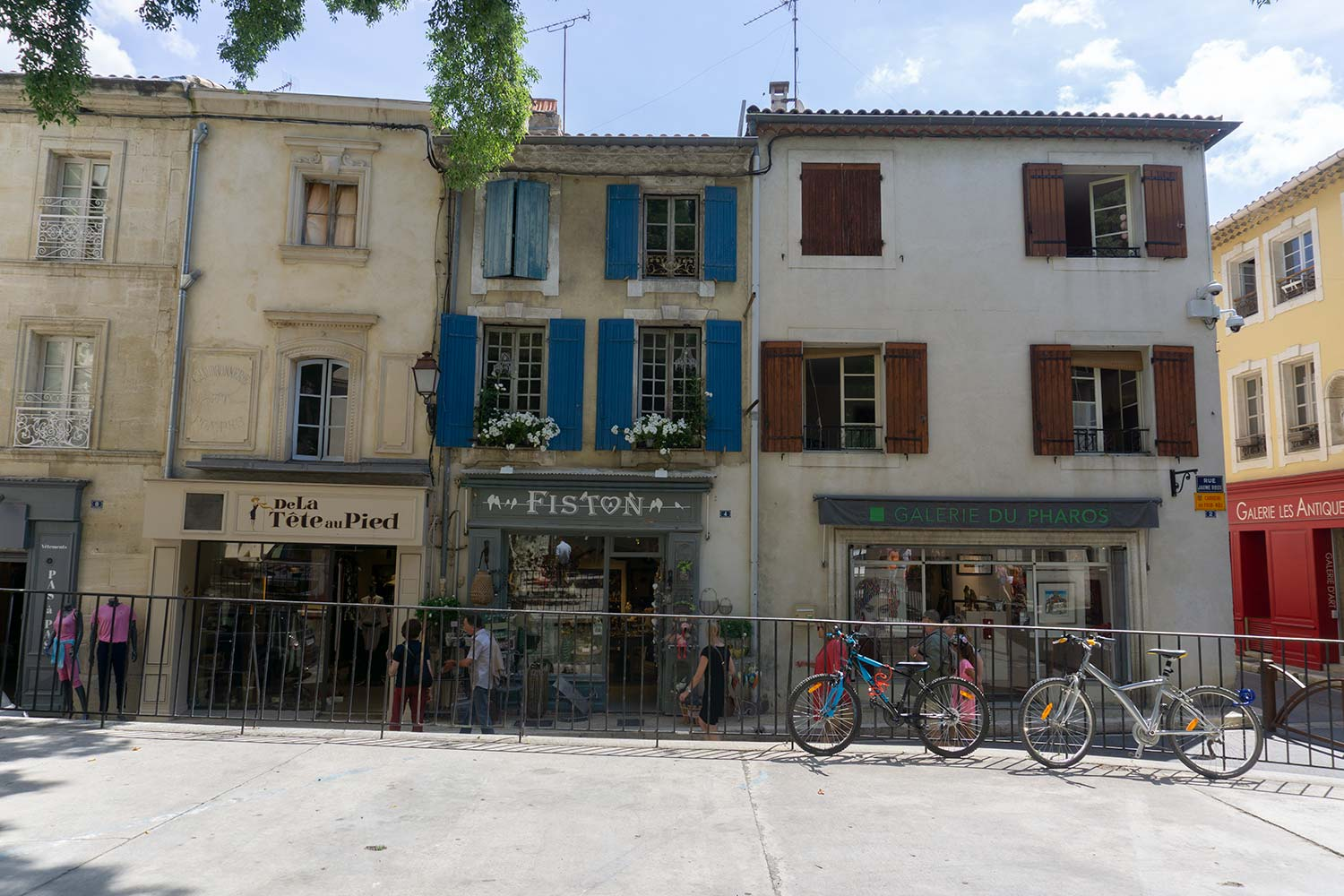A plaza in Saint-Remy surrounded by buildings with colorful shutters. Two bikes are resting against a railing.