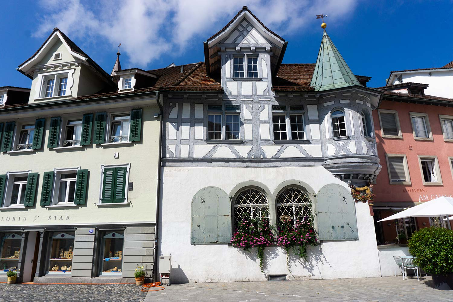 A cute white house with blue shutters in St. Gallen, Switzerland.