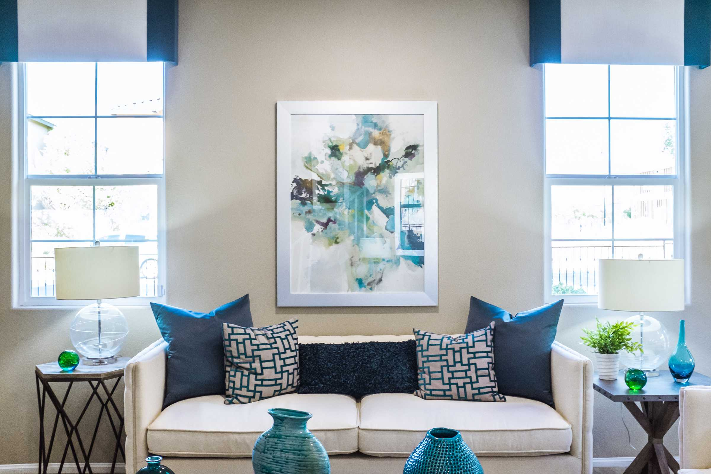 A white couch with blue pillows, two tables and a picture frame on the wall.