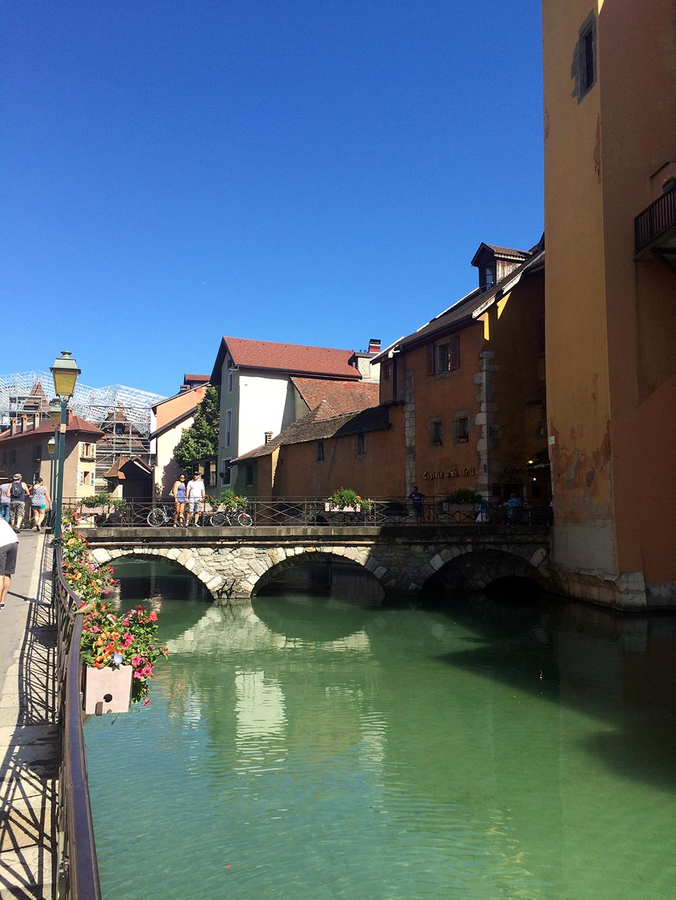 A bridge with flowers crossing a canal in Annecy, France. Colorful buildings are in the background.