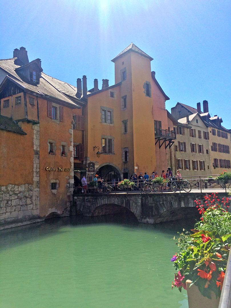 A canal in Annecy, France with colorful buildings and a bridge in the background.