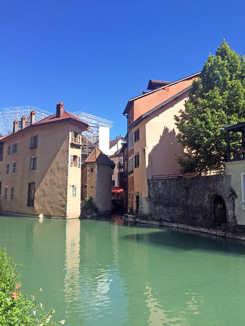 A canal in Annecy, France with colorful buildings in the background.