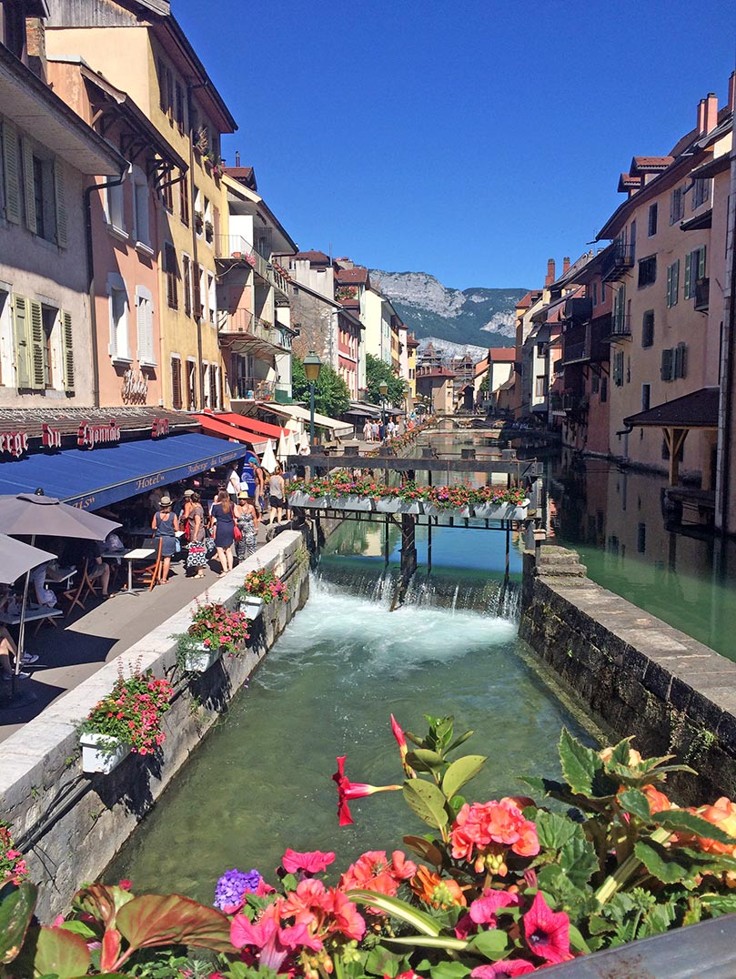 A canal in Annecy, France lined with colorful buildings and restaurants.