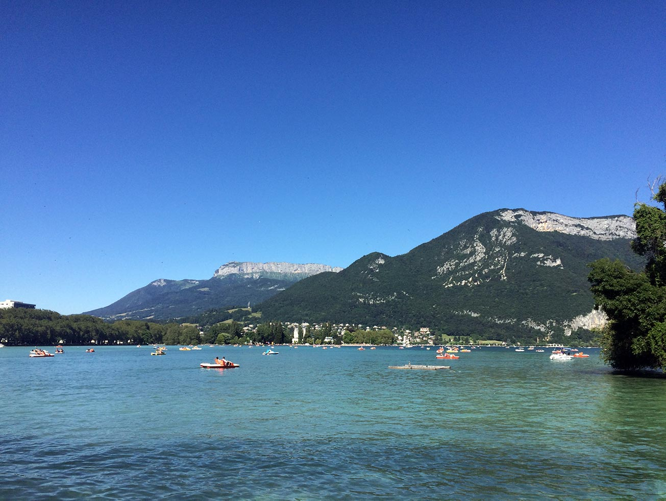 Lake Annecy with a mountain in the distance. There are boats out on the water.