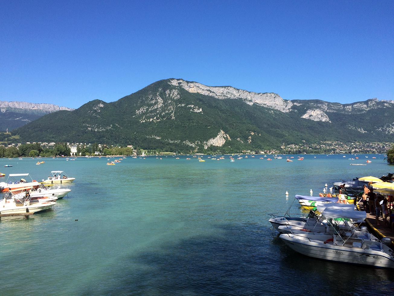 Lake Annecy with a mountain in the distance. There are boats docked and out on the water.