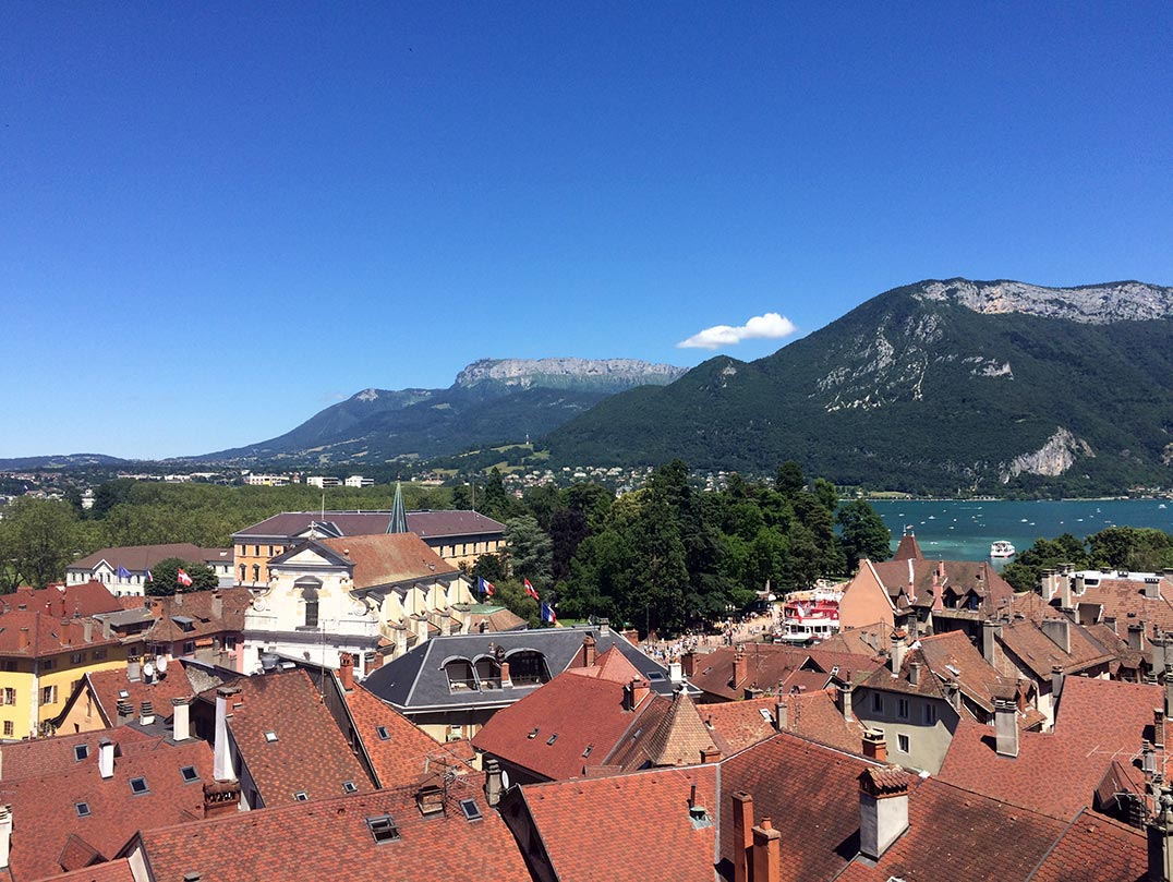 A view of the red rooftops in Annecy, France with the lake and mountains in the distance.