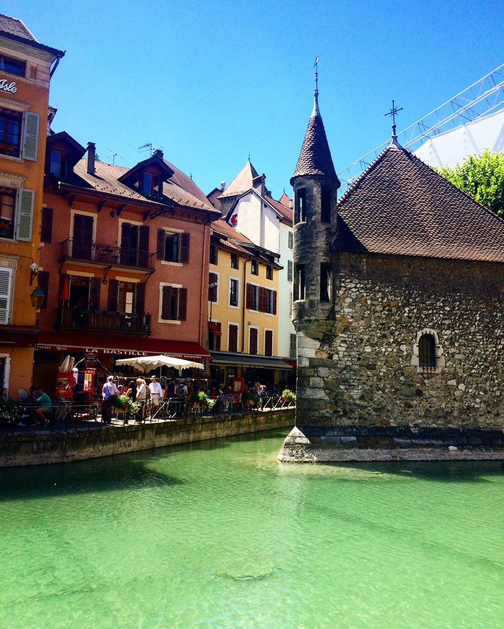 The canal in Annecy, France with the stone prison in the center. Colorful buildings are on the other side of the canal.