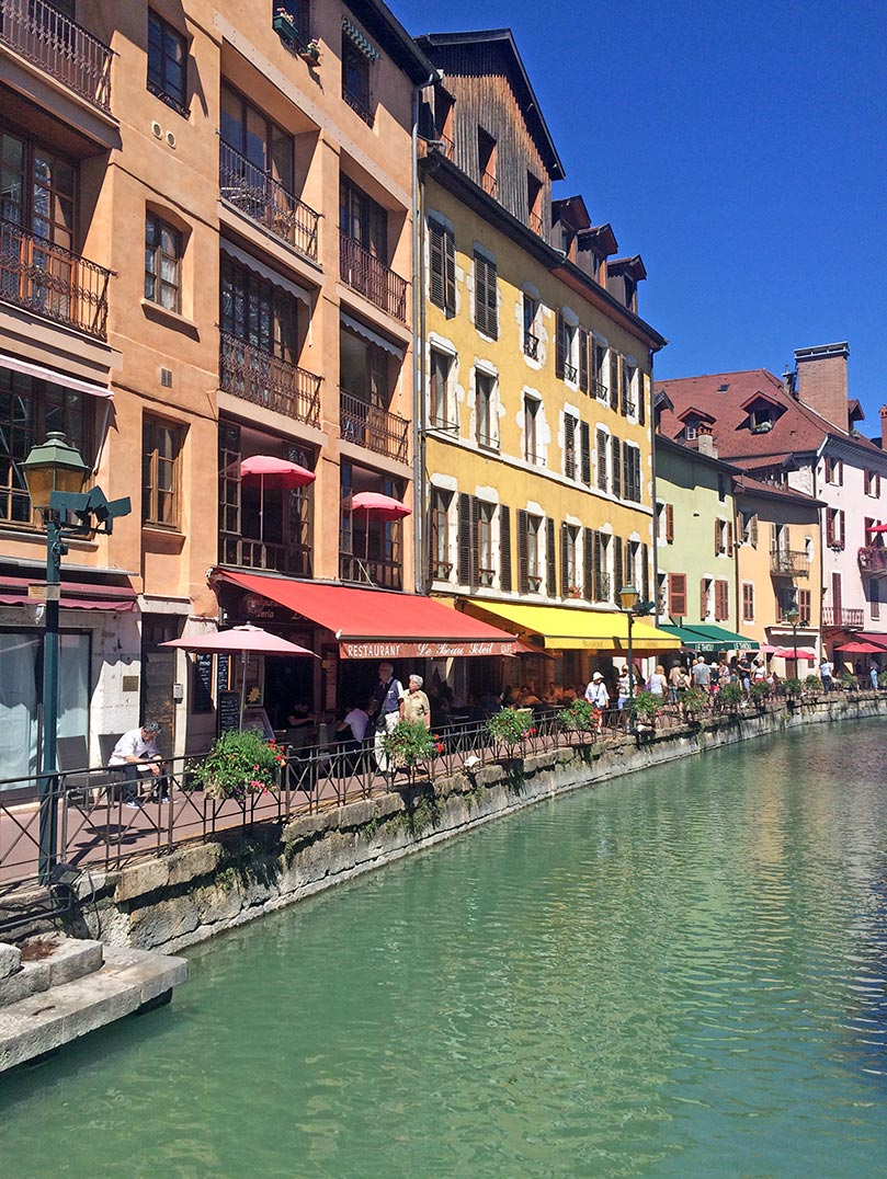 Colorful buildings lining a canal in Annecy, France.
