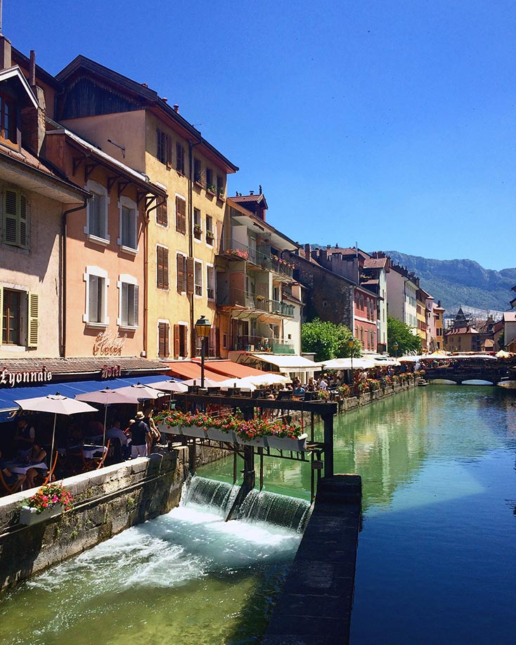 Restaurants lining a canal in Annecy, France. Mountains are seen in the background.