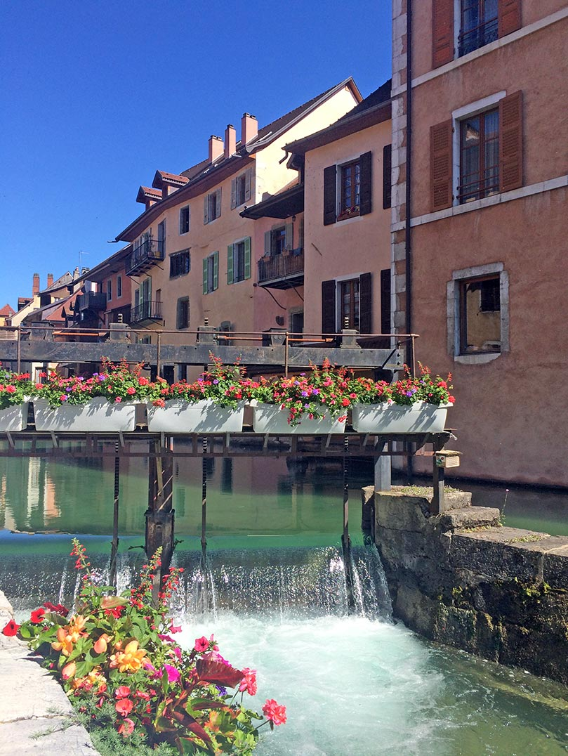 A canal in Annecy, France with flowers and colorful buildings in the background.