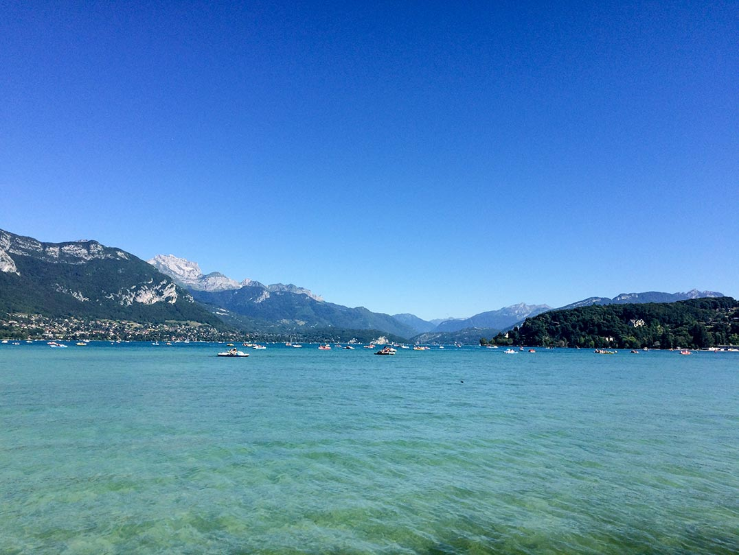 A lake with mountains in the background in Annecy, France.