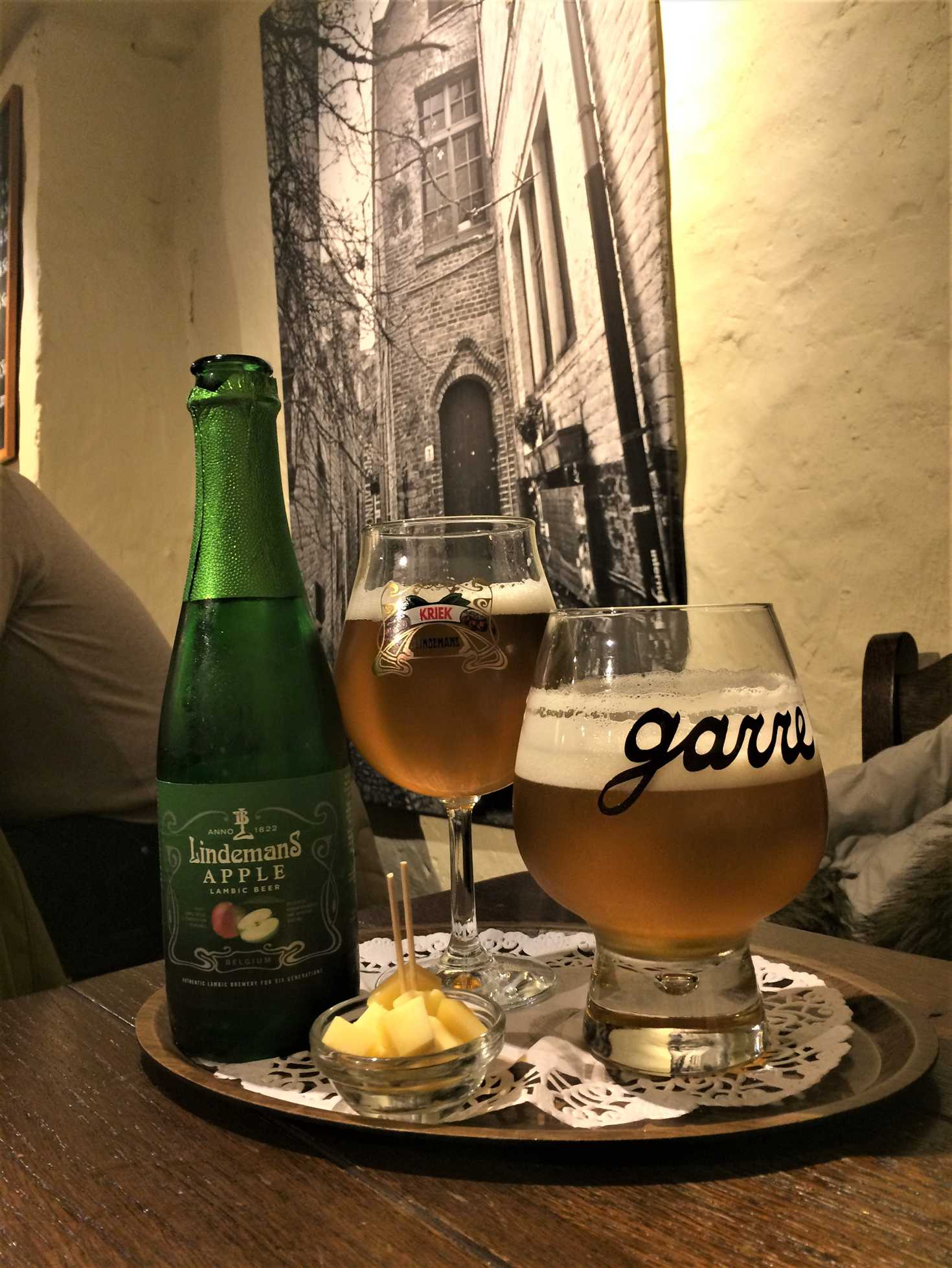 A picture of two glasses of beer, a bottle of lindman's apple lambic beer, and a small dish filled with cubed cheese.