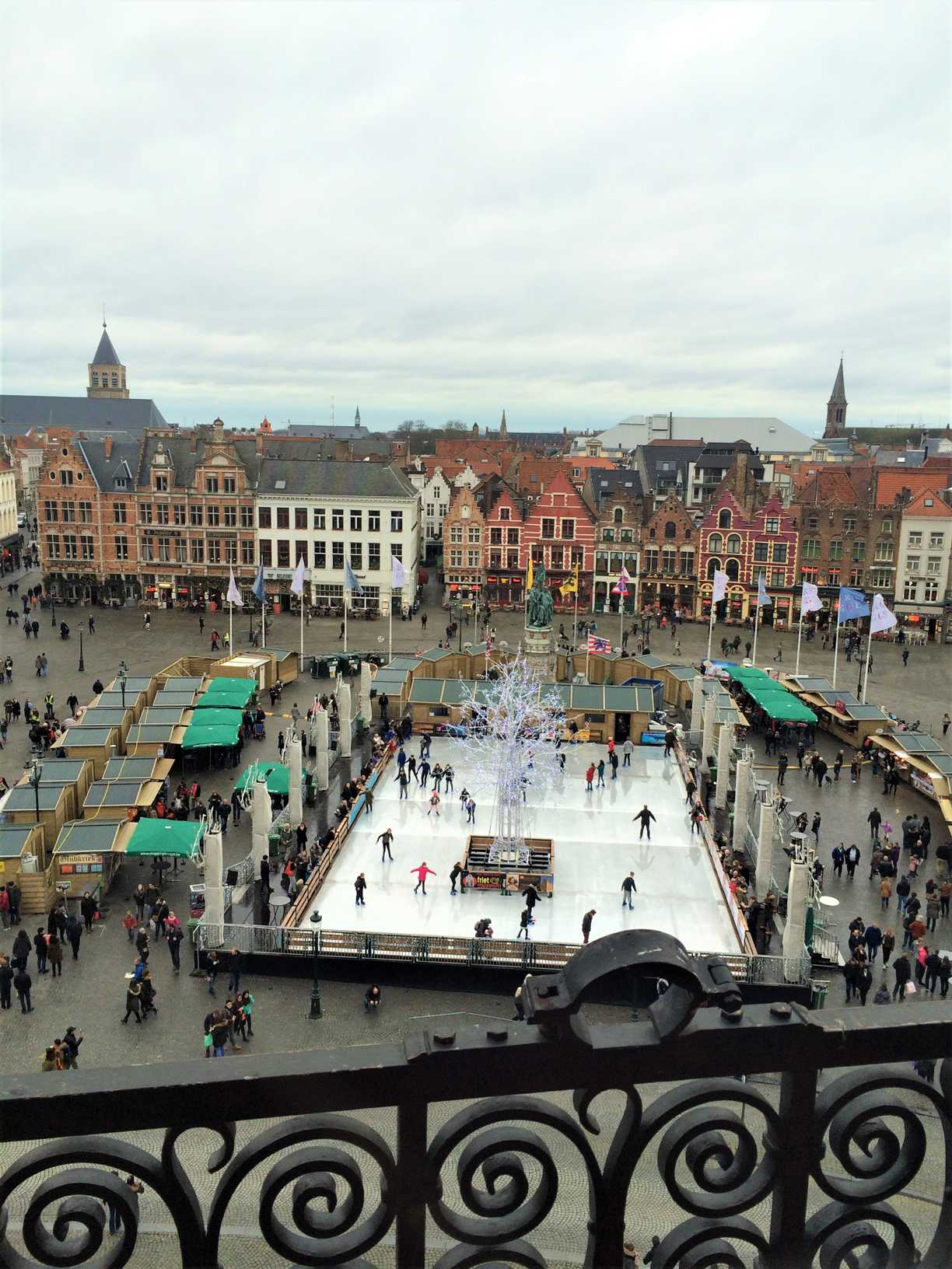 A picture of and ice rink and buildings in Markt in Bruges, Belgium, as seen from the belfry.