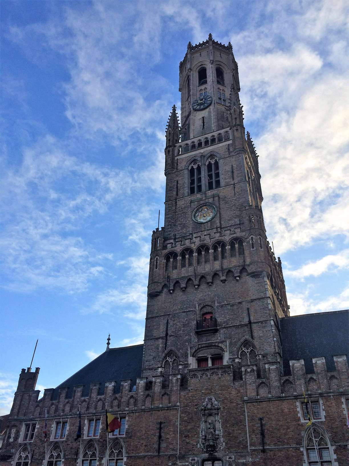 A picture of the belfry in Bruges, Belgium with a blue sky and some clouds in the background.