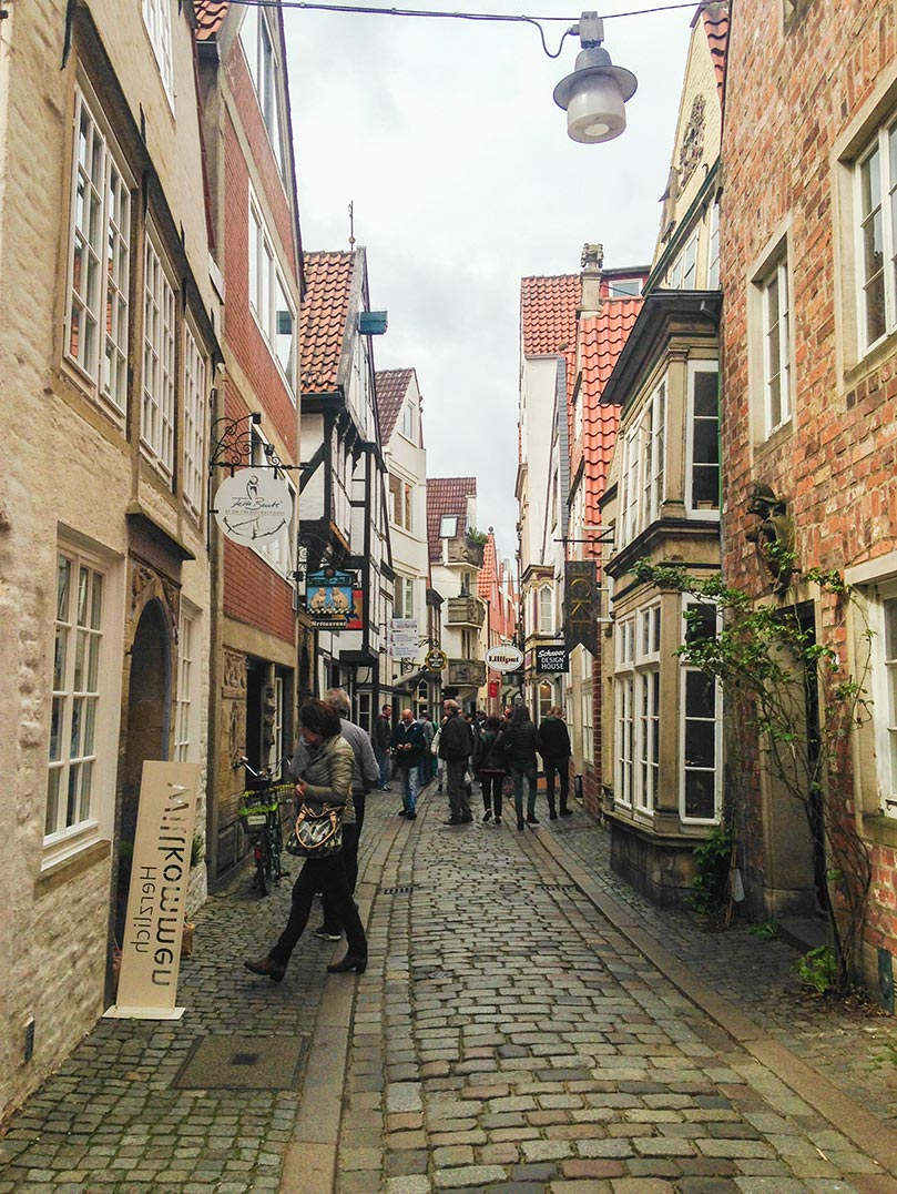 A narrow street in Bremen, Germany with cobblestones.