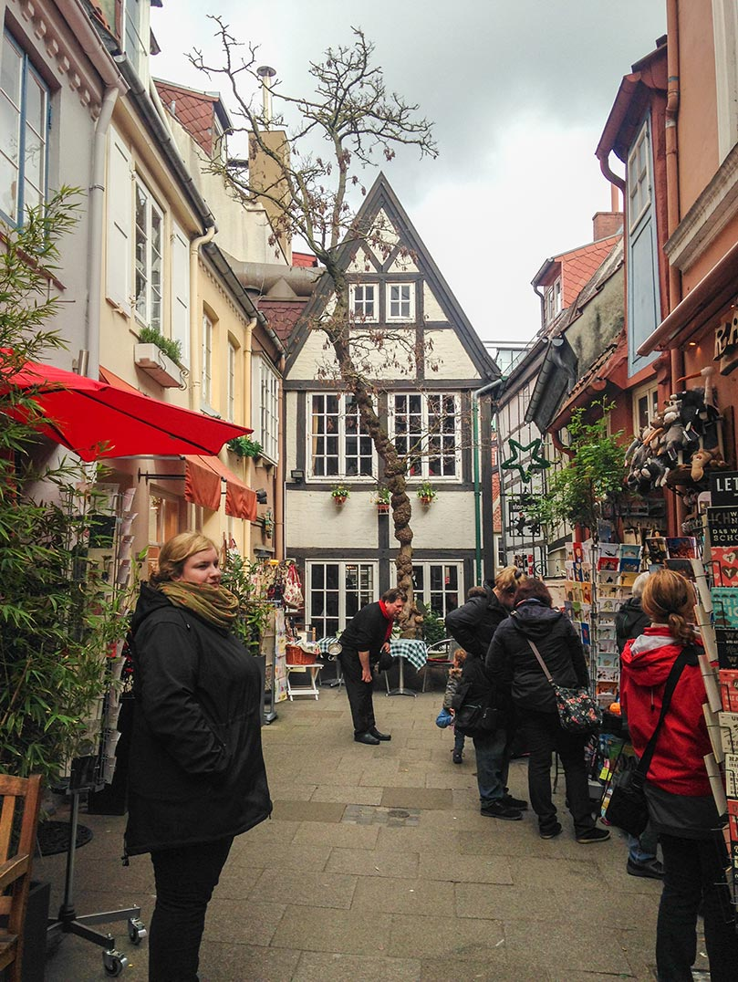 A street in Bremen, Germany with a narrow timbered house at the end of the street.