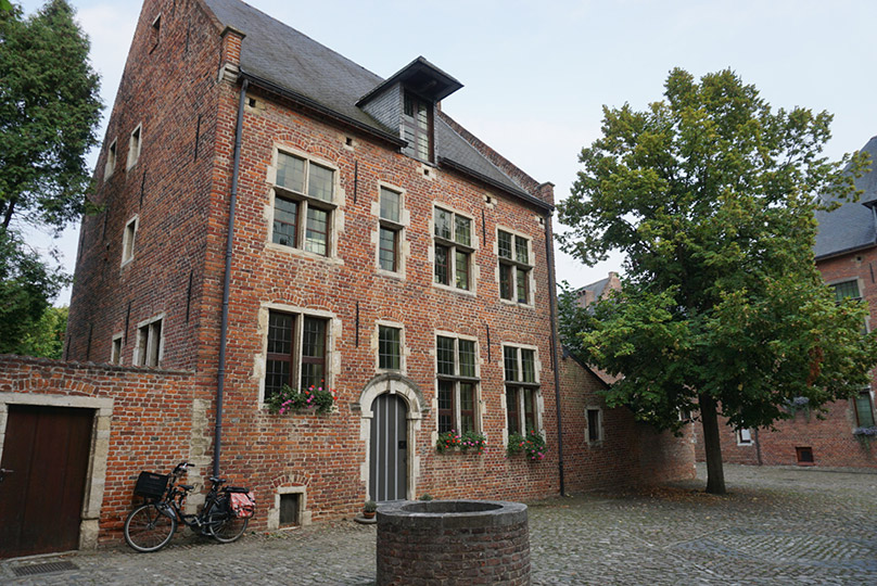 A brick house and courtyard with a tree and well in Leuven, Belgium.