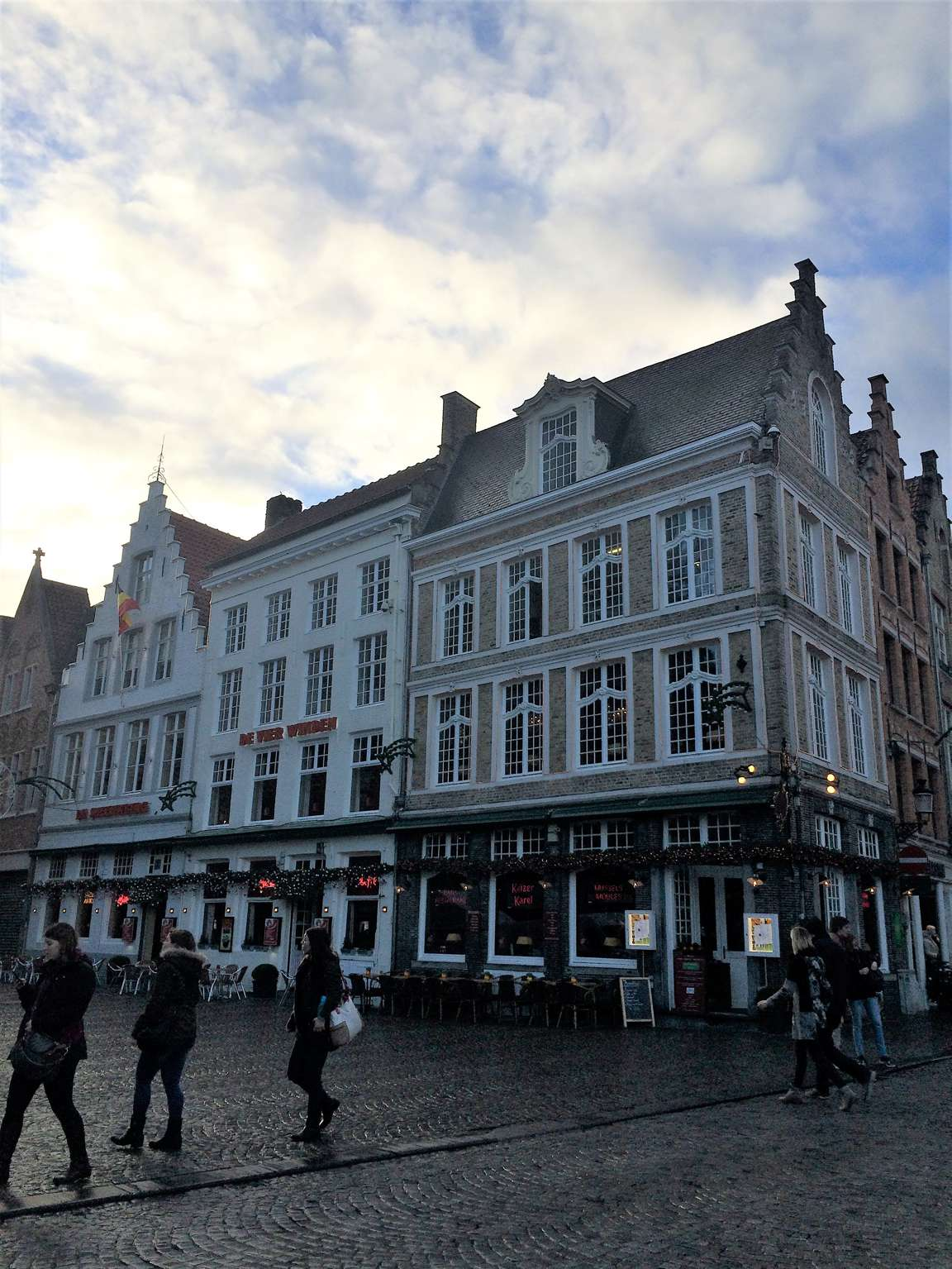 A picture of a street in Bruges, Belgium with gabled buildings and cobblestone streets.