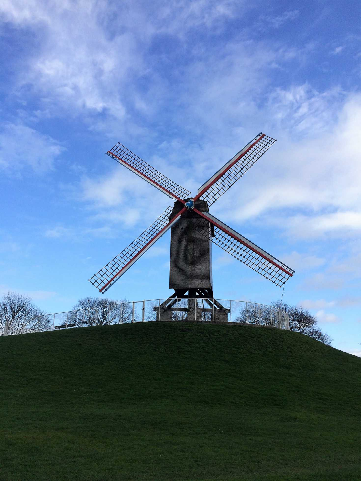 A picture of a windmill with a blue sky and green grass in Bruges, Belgium.