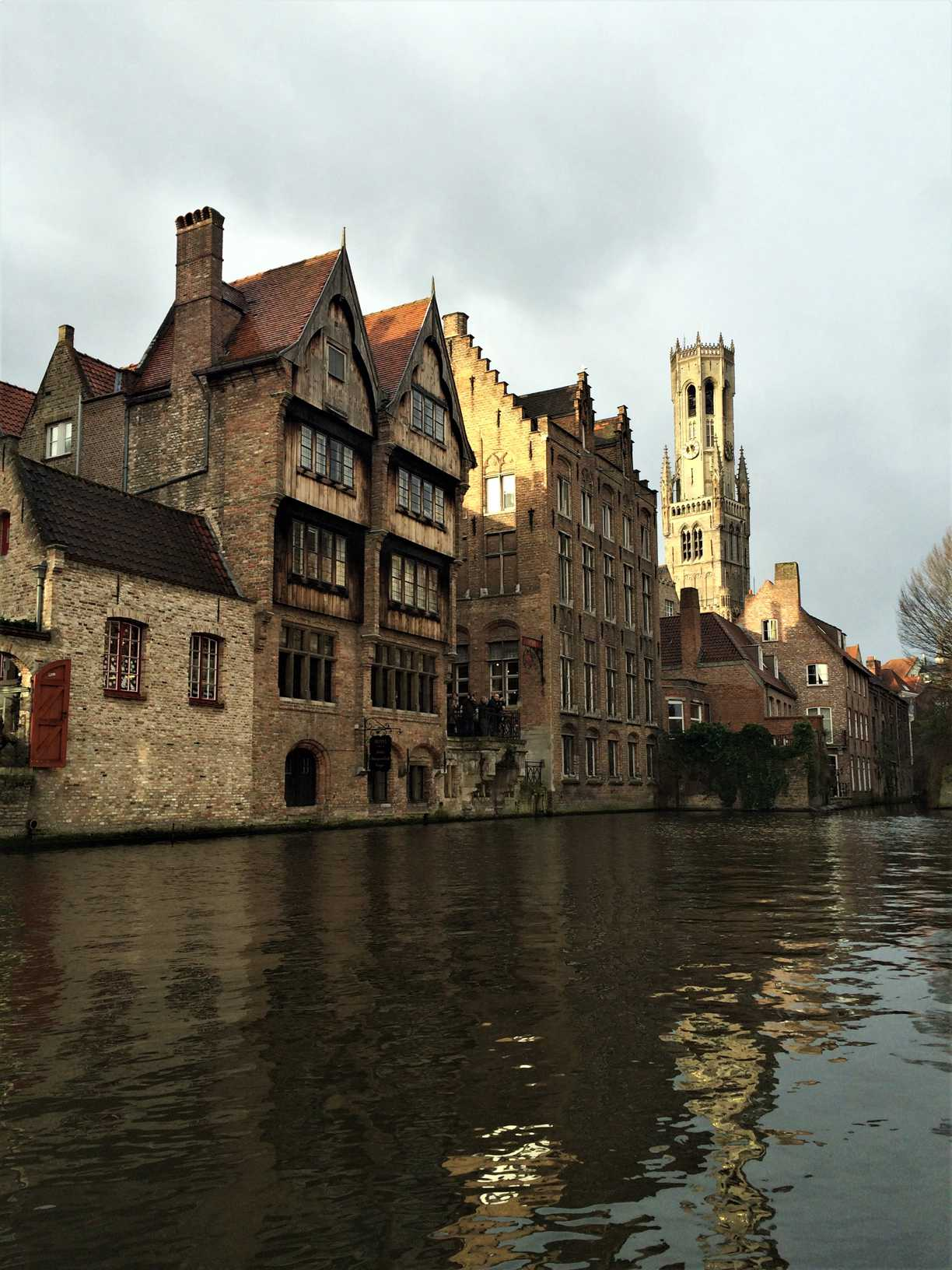 A picture of the oldest wooden buildings in Bruges, Belgium as seen from a boat on the canal.