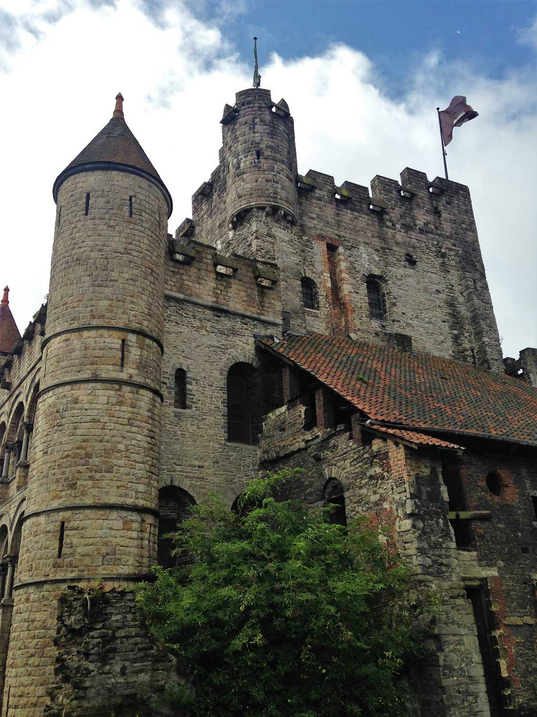 A picture of Gravensteen castle in Ghent, Belgium with flags flying.
