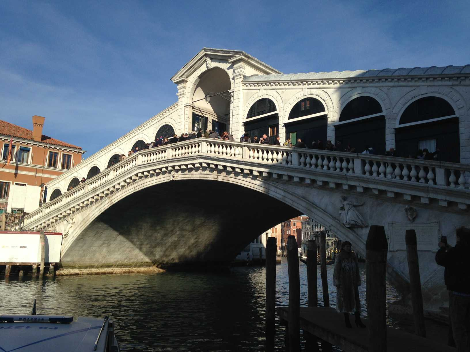 The Rialto Bridge in Venice, Italy full of people.