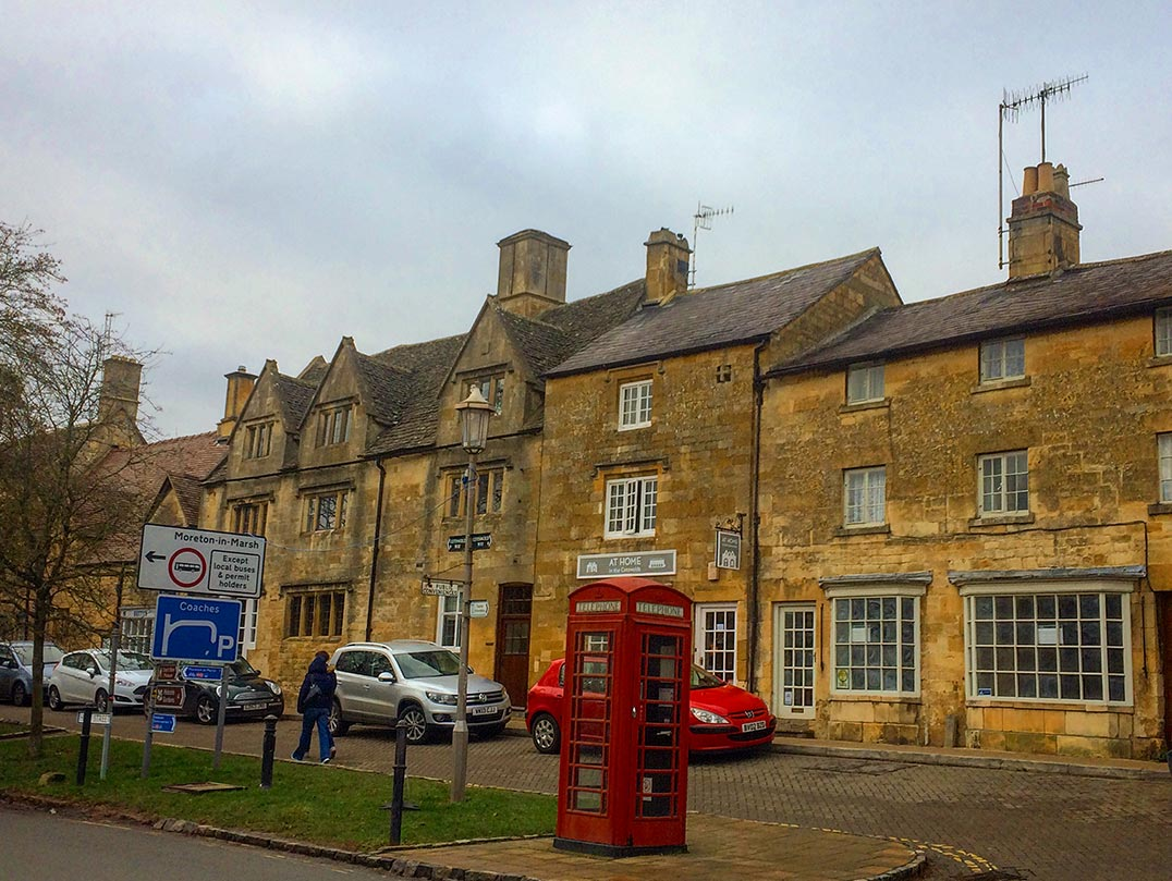 Stone buildings and a red telephone booth in the Cotswolds, England.
