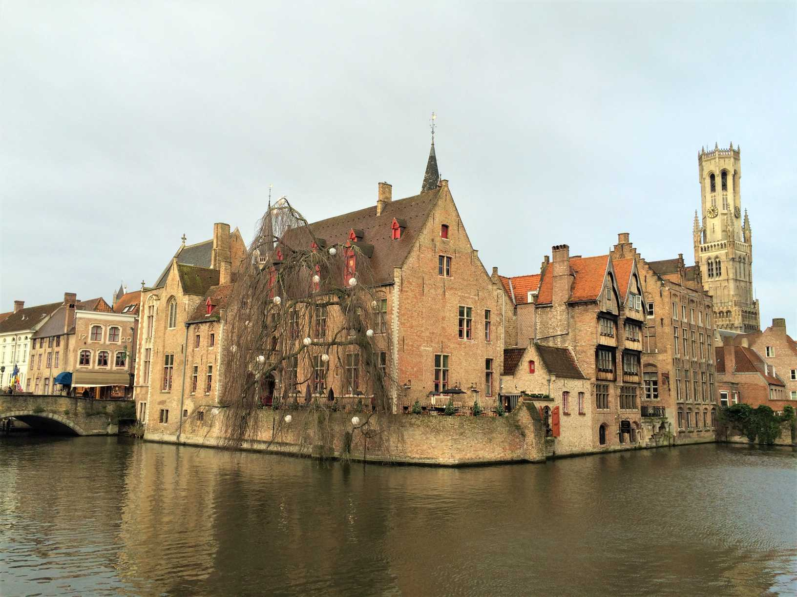 A picture of buildings on a canal in Bruges with a tower in the background.