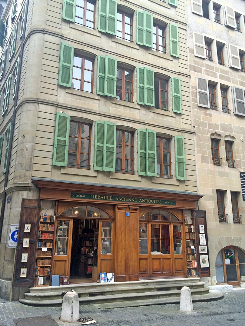 A stone building with green shutters in Geneva, Switzerland. There is a bookstore at the bottom with a wooden store front and books outside.