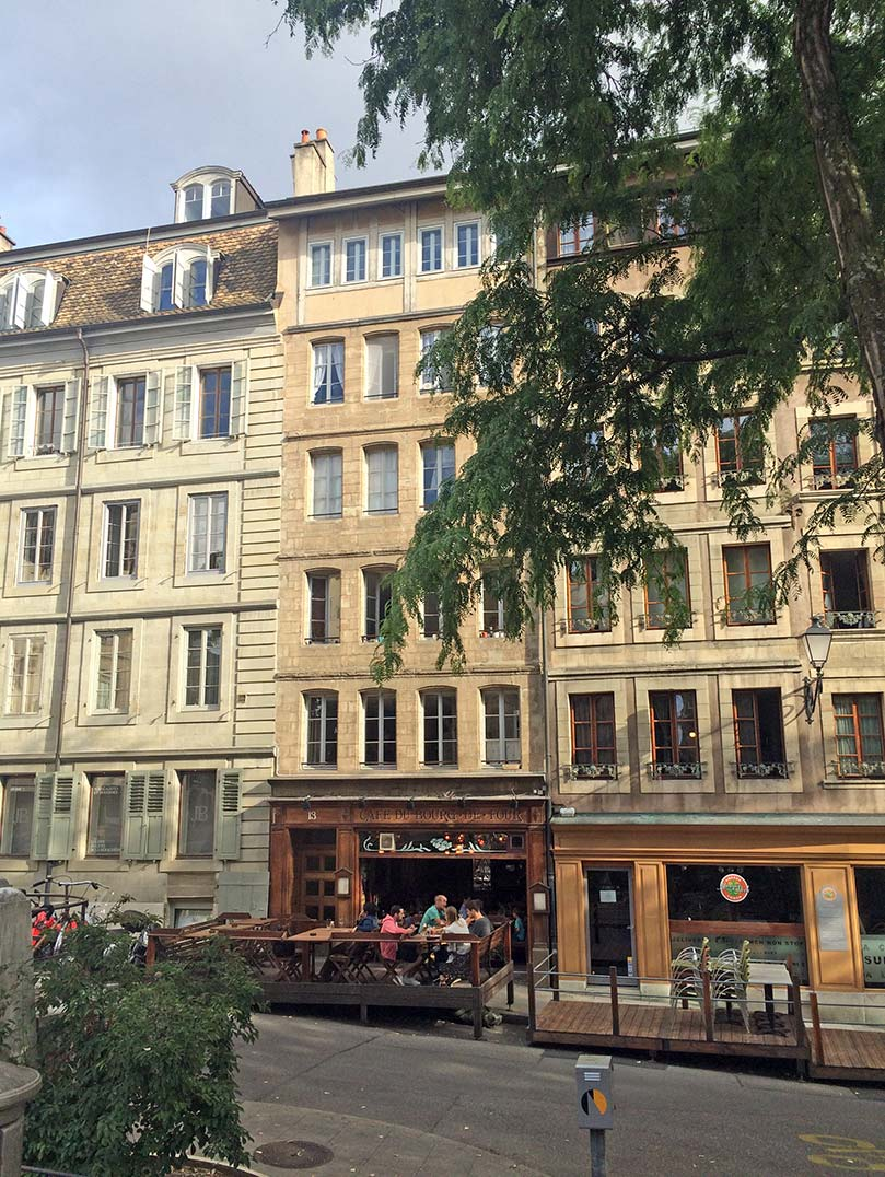 Stone buildings in Geneva, Switzerland with restuarants in front of them.