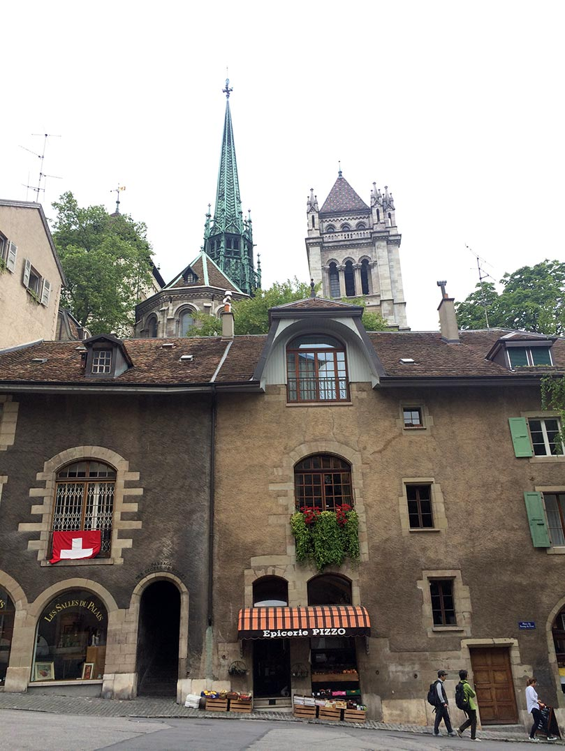 Traditional looking buildings in Switzerland with a green, copper church steeple in the background.