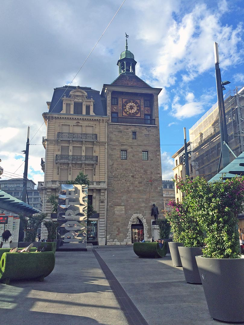 A stone clock tower in Geneva, Switzerland on a partly cloudy day.