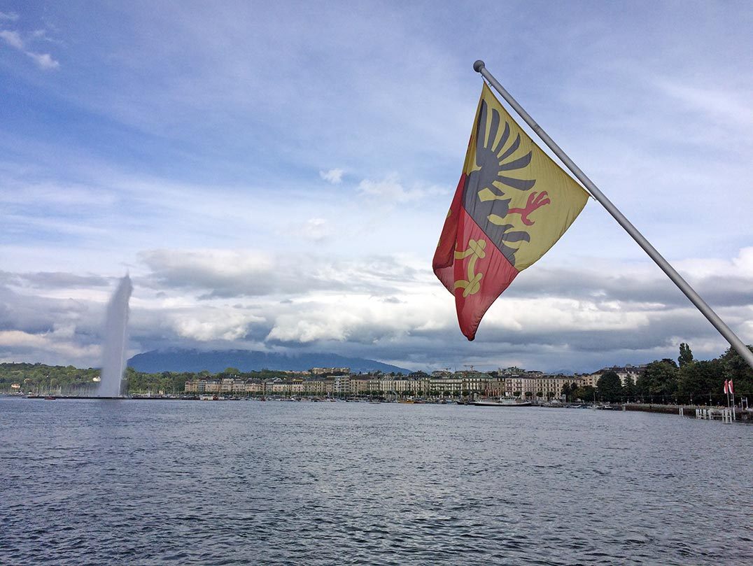 A view of Lake Geneva, the Jet d'Eau with the city of Geneva in the distance. In the forefront is the flag of Geneva.
