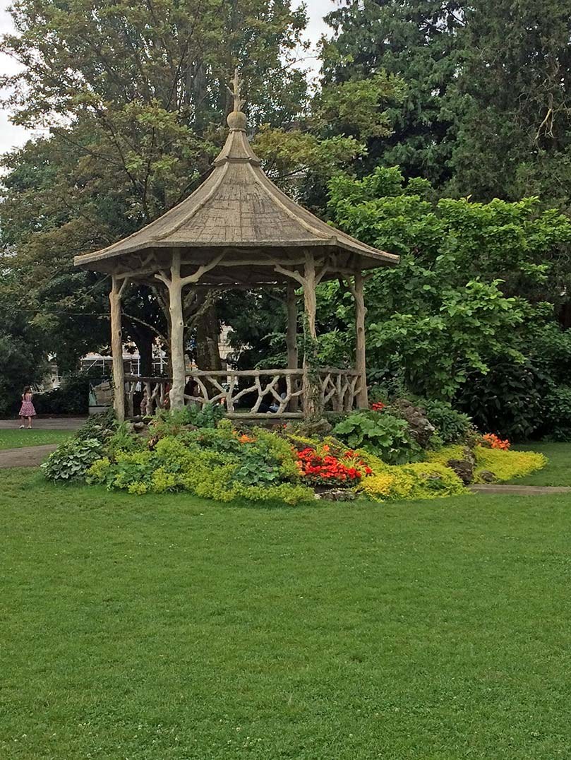 A wooden gazebo with plants surrounding it in Parc d'Anglais in Geneva, Switzerland.