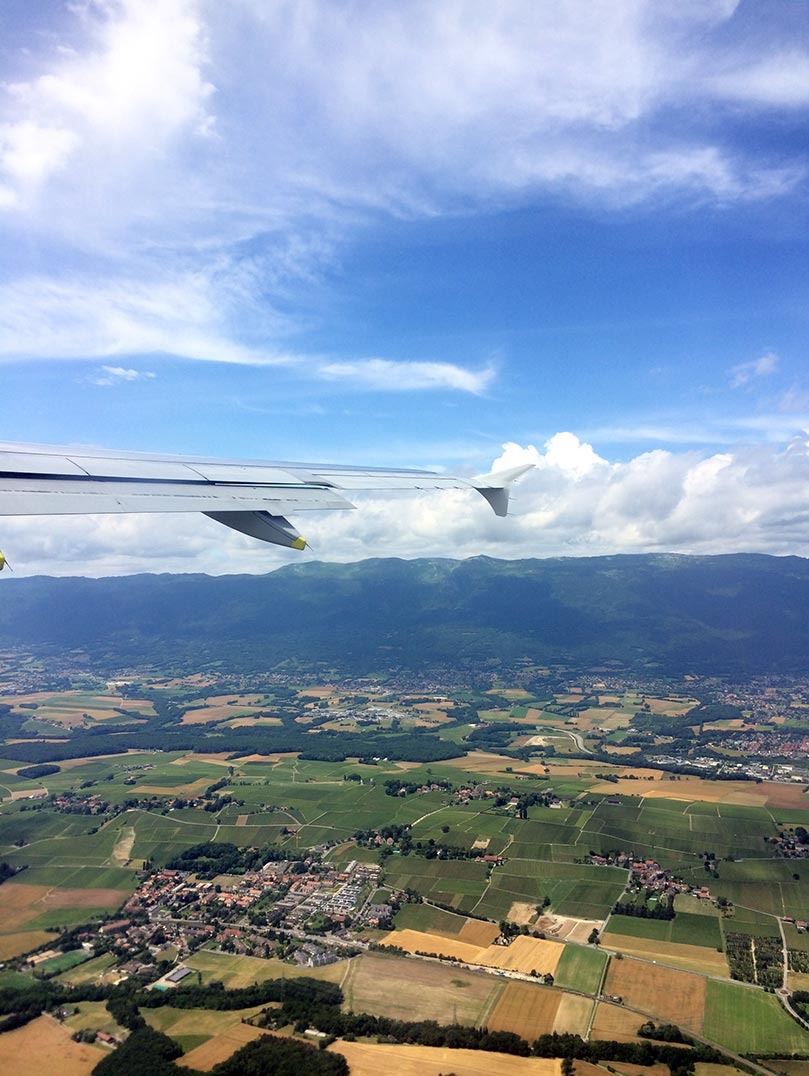 The green countryside and hills of Switzerland as seen from an plane.