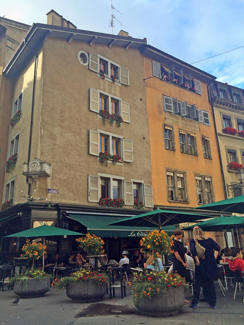 Colorful buildings in Geneva, Switzerland with green umbrellas for restuarants lining the street.